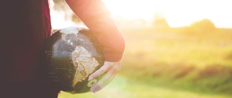 Woman holding a globe of World in her hand.
