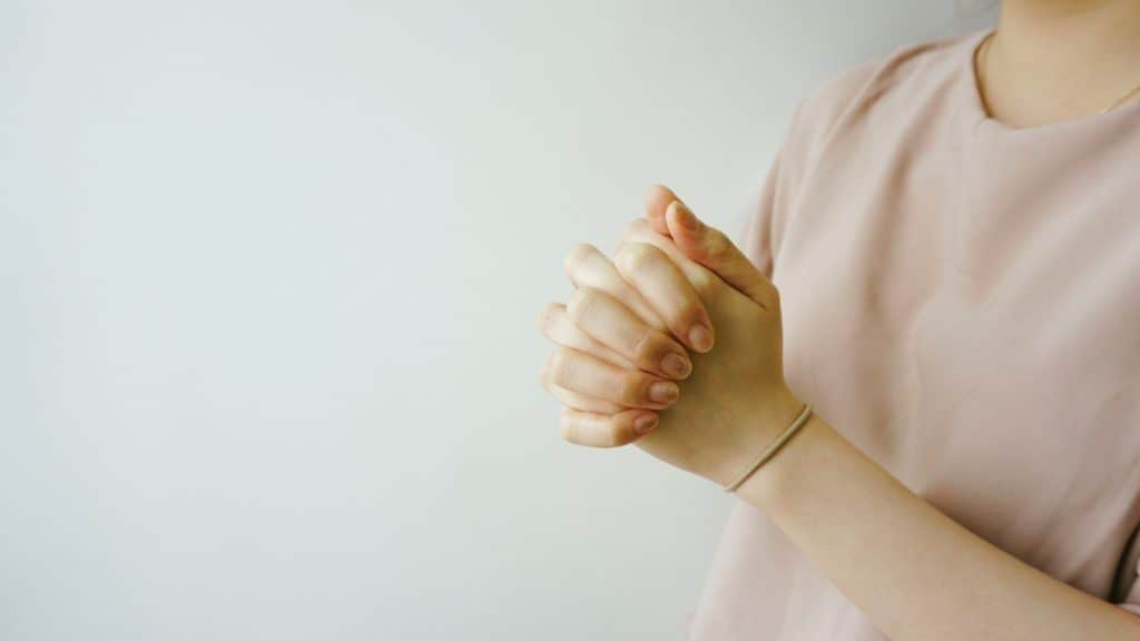 Woman standing with clasped hands